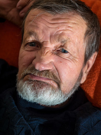 Close-Up Of Senior Man Lying On Bed At Home