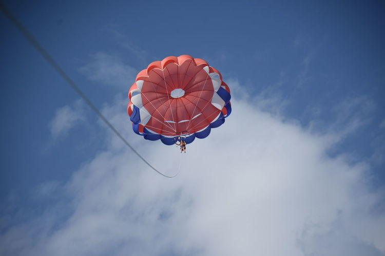Low angle view of woman paragliding against sky