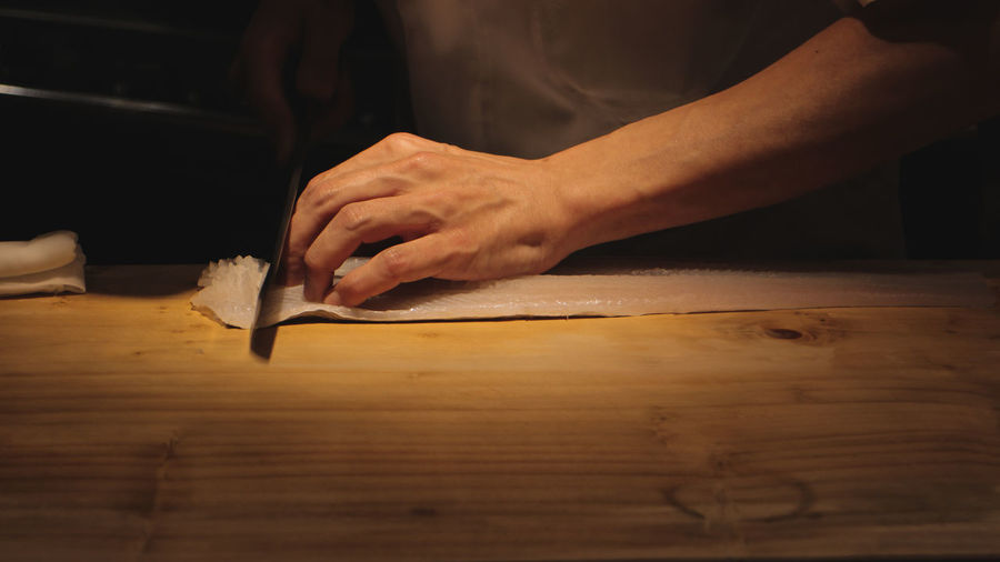 Master Chef cutting freshwater eel Butcher Chopping Close-up Cutting Board Day Food Freshness Holding Human Body Part Human Hand Indoors  Men Midsection Musical Instrument Occupation One Person People Preparation  Real People Skill  Wood - Material