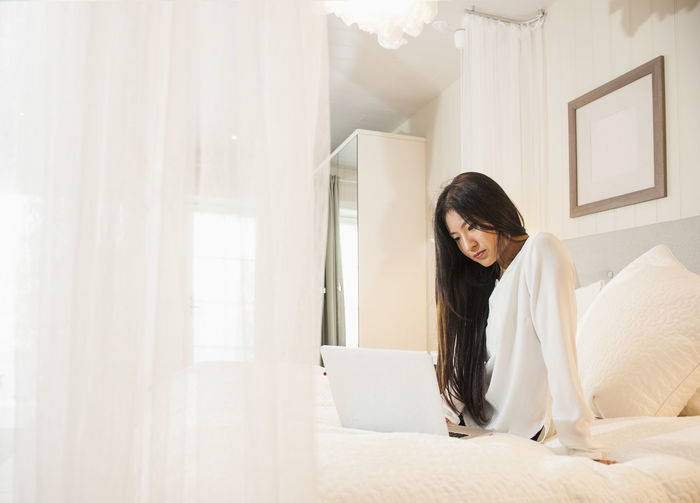Young woman using laptop on bed at home