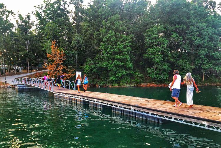 People on lake against trees