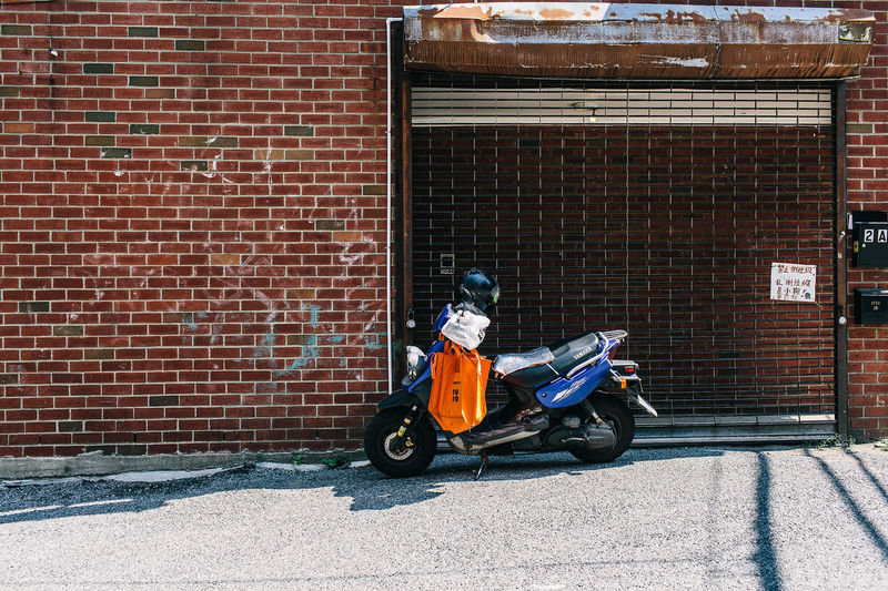 Motor scooter parked on street against building