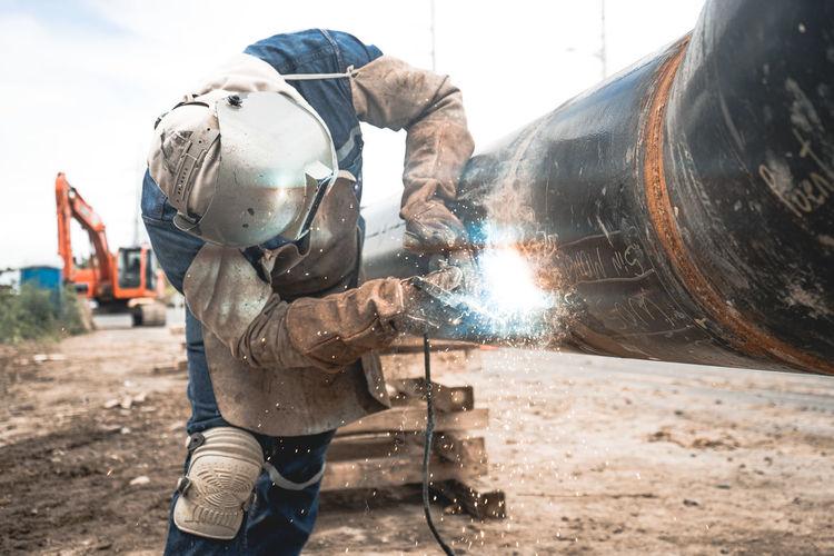 Man working on metal welding water pipe