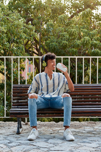 Young man sitting on bench in park