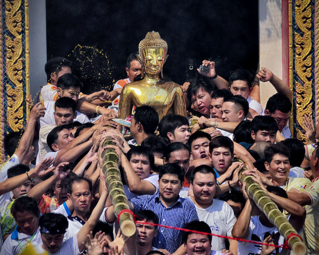 People by buddha statue in city during event