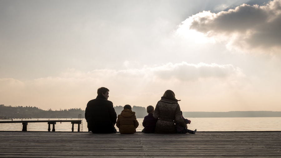 Rear view of parents with children sitting on pier over lake at sunset