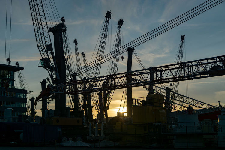 silhouette of cranes in the harbor of rostock Sky Machinery Industry Cloud - Sky Construction Industry Built Structure Crane - Construction Machinery Transportation Development No People Architecture Low Angle View Sunset Nature Construction Site Building Exterior Incomplete Outdoors Silhouette Commercial Dock Construction Equipment Silhouette