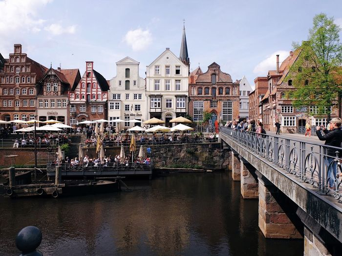 Group of people on bridge over river against buildings in city