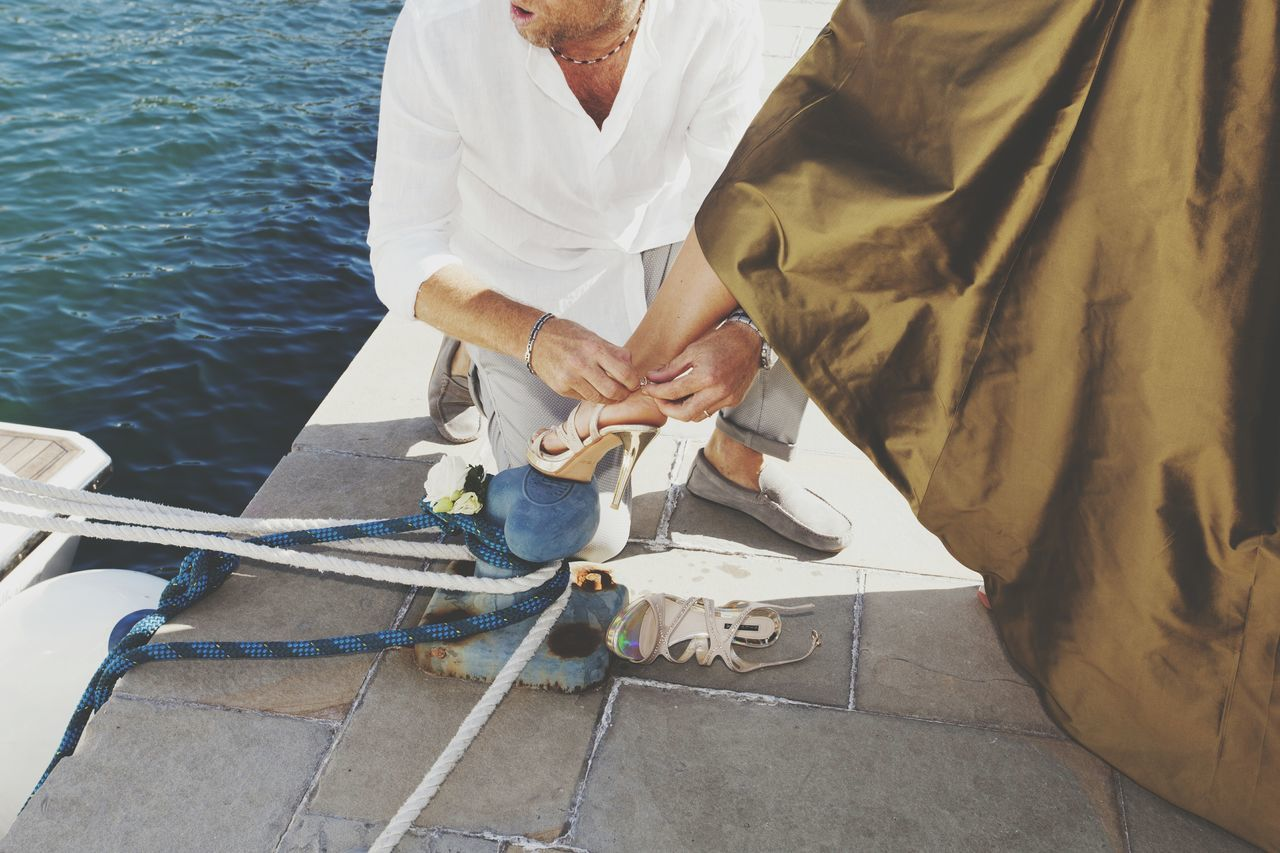 Low section of bridegroom putting high heel on bride's foot at pier