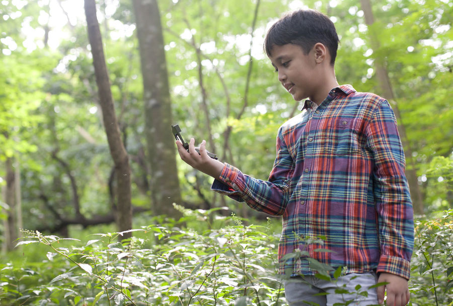 Young Boy with Compass 9-11 Asian  Boy Color Image Compass Direction Forest Guidance INDONESIA Morning Nature Navigational Compass One Person Outdoors People Standing Tree Young Adult