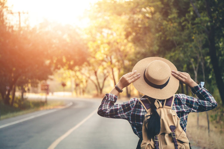 Rear view of woman wearing hat standing on road