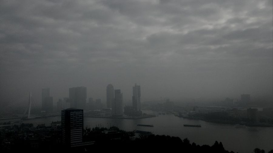 High Angle View Of River By Buildings Against Cloudy Sky