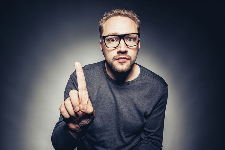 Nerd with black glasses gesturing with his finger Attention Surprised Thinking Adult Beard Bearded Casual Clothing Close-up Eyeglasses  Eyeglasses  Front View Gesturing Gray Background Human Body Part Human Hand Looking At Camera Men Nerd One Person People Portrait Real People Studio Shot Thumbs Up Young Adult