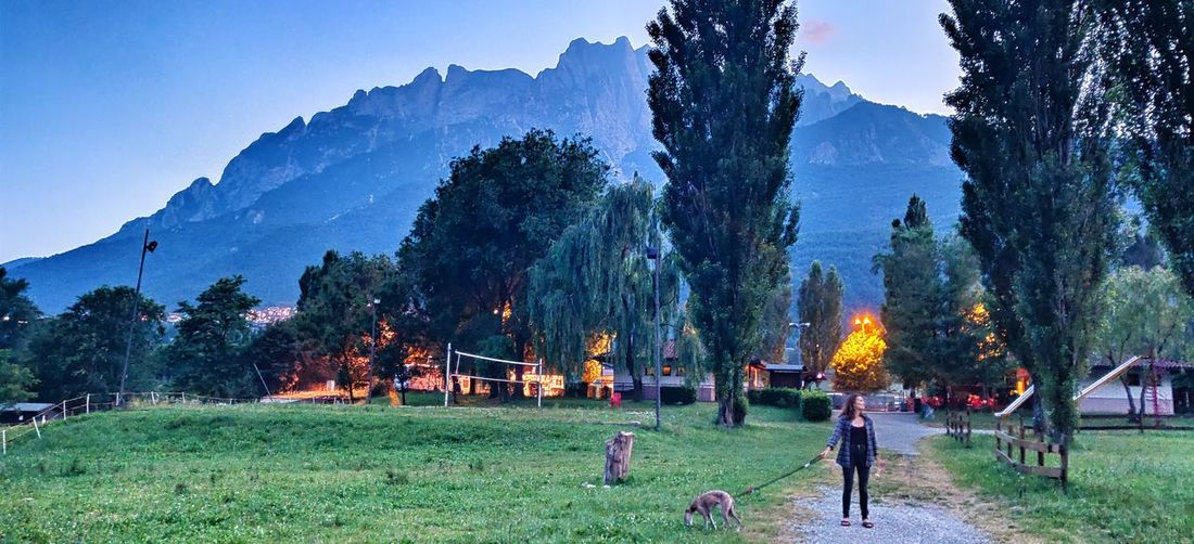 People on field against trees and mountains