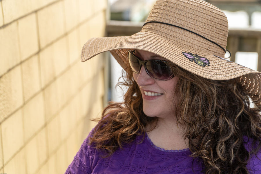 Hat Brunette Casual Clothing Clothing Day Fashion Front View Glasses Hair Hairstyle Happiness Headshot Leisure Activity Lifestyles Long Hair One Person Portrait Real People Smile Smiling Wall - Building Feature Women Young Adult