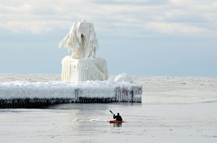 a extreame sportsman paddles a kayack around The lighthouse in St Joe Michigan which is covered in layers of ice, Architecture Frozen Great Lakes Ice Ice Sculpture Lake Michigan Lighthouse Man St Joseph MI Lighthouse Travel USA Art Beauty In Nature Building Day Horizon Over Water Kayak Lighthouse_lovers Nature Outdoors Scenics Seasonal Sky Snow Sports Go Higher