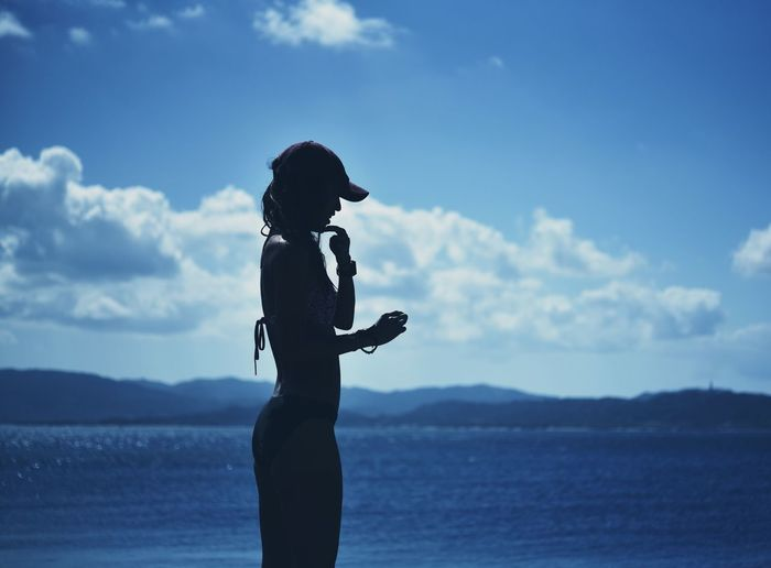 Side view of woman standing by sea against sky