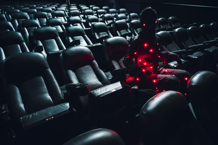 Man sitting with illuminated string lights on seat