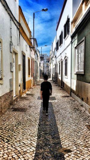 Rear view of man walking on street in town