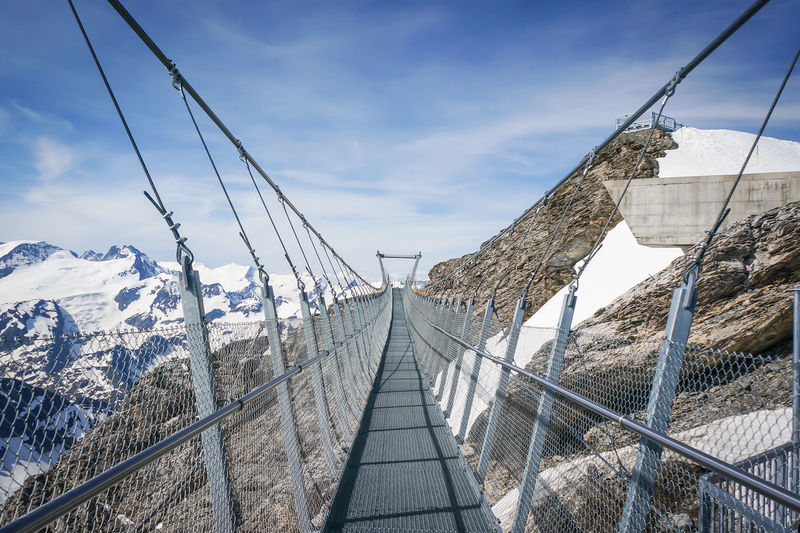 TITLIS Cliff Walk. Blue Bridge - Man Made Structure Built Structure Cable Cliff Walk Cloud Cloud - Sky Connection Day Diminishing Perspective Engineering Mountain Nature No People Outdoors Season  Sky The Way Forward Travel Destinations Vanishing Point Weather