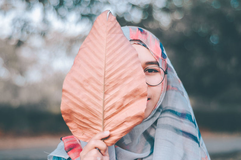 Close-up portrait of teenage girl covering face with dry leaf