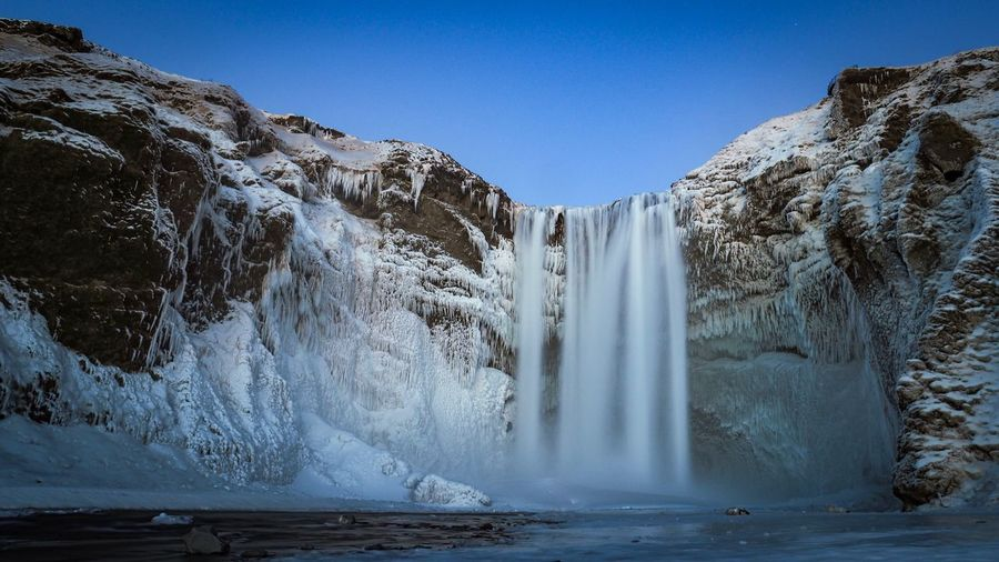 Scenic view of waterfall against clear sky during winter