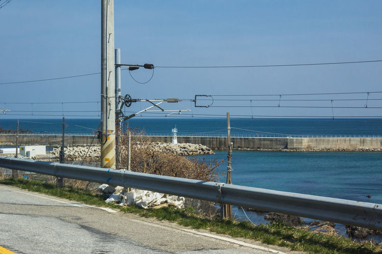 Road by sea against clear blue sky