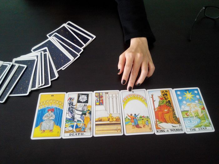 Fortune teller sitting in front of tarot cards on table