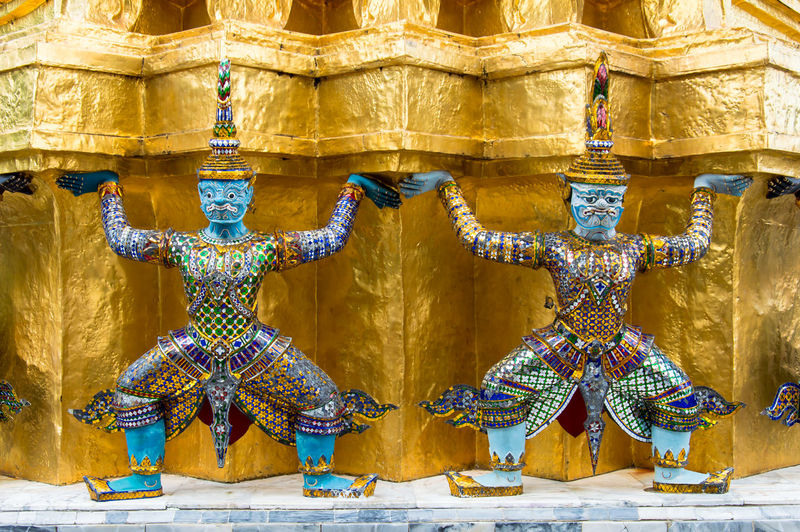 Close-up of demon statue against gold wall at wat phra kaew