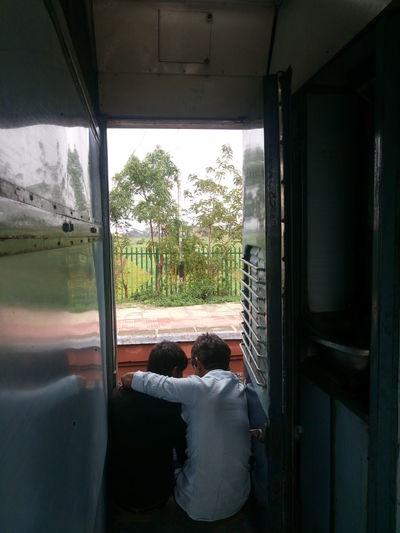 Rear view of men sitting on train doorway