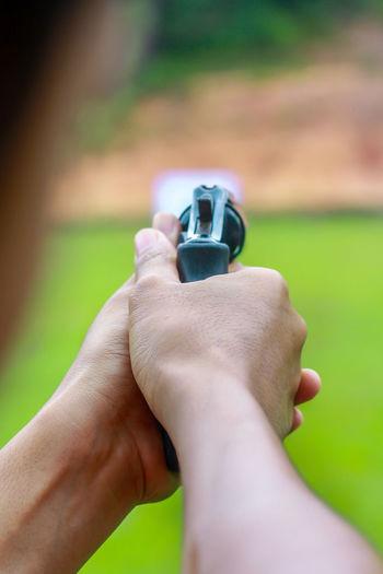 Close-up of hand aiming gun at target