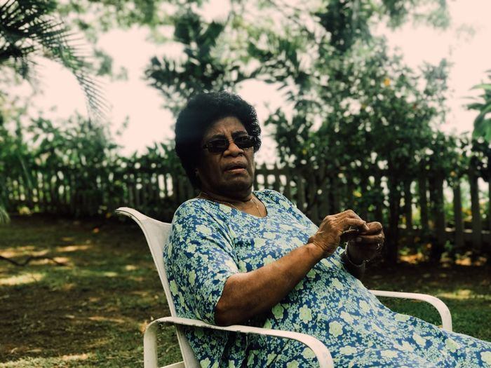 Portrait Of Woman Sitting On Chair In Yard