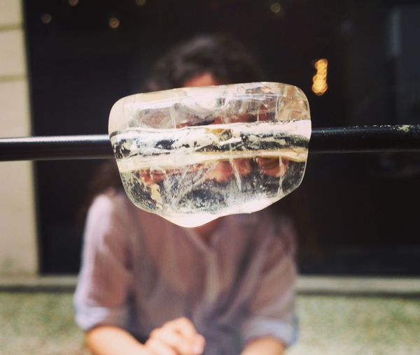 Close-Up Of Ice Cube On Rod Against Woman