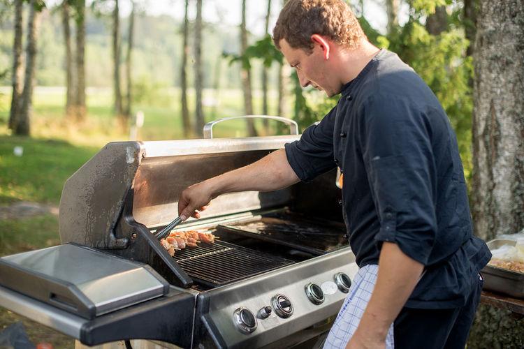 Man preparing food on barbecue against trees