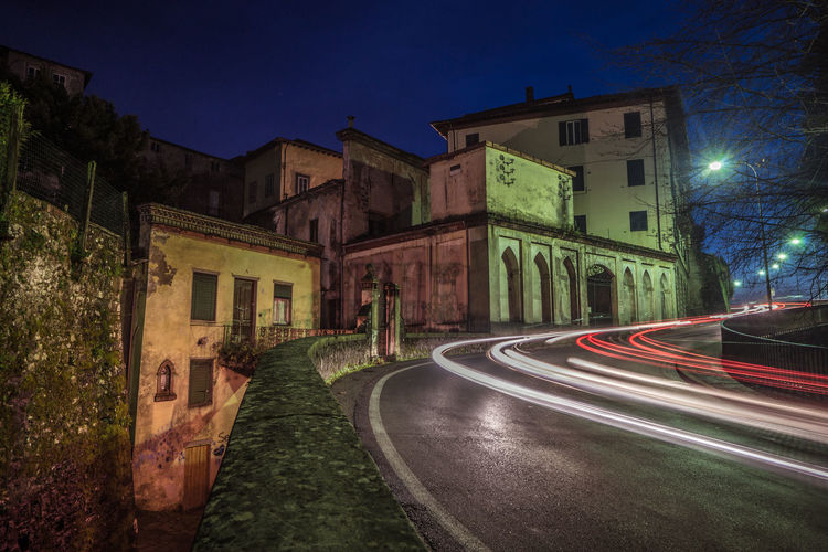 View of road along buildings at night