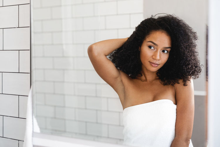 Young Woman Wrapped In Towel Standing Against Wall