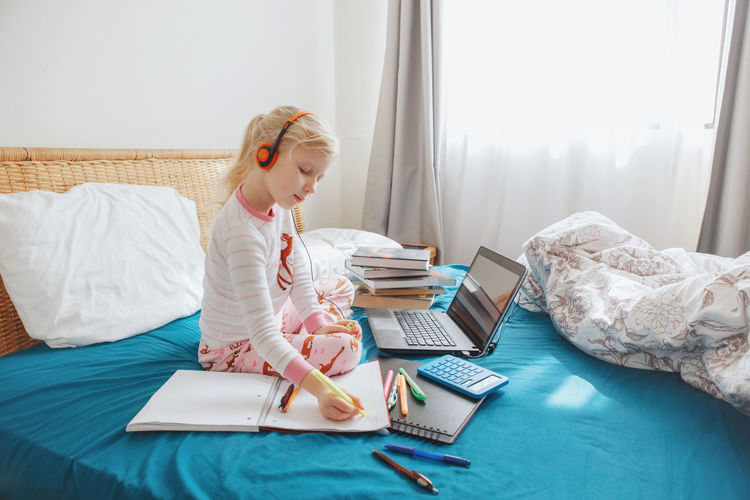 Rear view of girl using laptop on bed at home