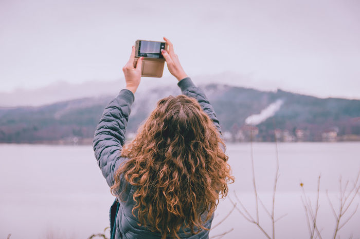 Taking Photos Mobile Phone Holding Phone Woman Girl Long Hair Curly Hair Landscspe Nature Device Phone Taking Selfies Adults Only People Portable Information Device Day Outdoors One Person Camera - Photographic Equipment Lake Rear View Fresh On Market 2018