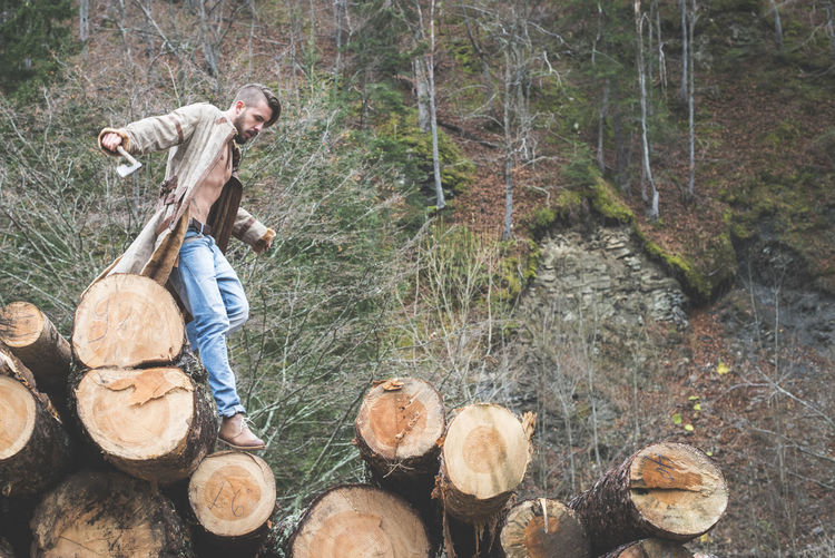 Mountain Men Young Adult Young Boy Forest Dress Timber Woods Walking Dog Jeans Tree Log Firewood Nature Wood - Material Wood Land Deforestation Plant Day Lumber Industry Full Length Stack WoodLand Leisure Activity Real People Outdoors People