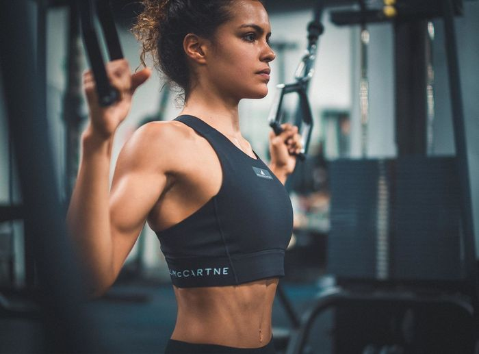 Woman Power Adult Body Conscious Clothing Determination Effort Exercising Fitgirl Focus On Foreground Gym Healthy Lifestyle Indoors  Lifestyles Muscular Build Muscular Woman One Person Real People Sport Sports Clothing Sports Training Strength Weight Weight Training  Young Adult Young Women