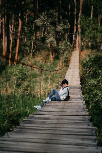 Man photographing while sitting on rope bridge