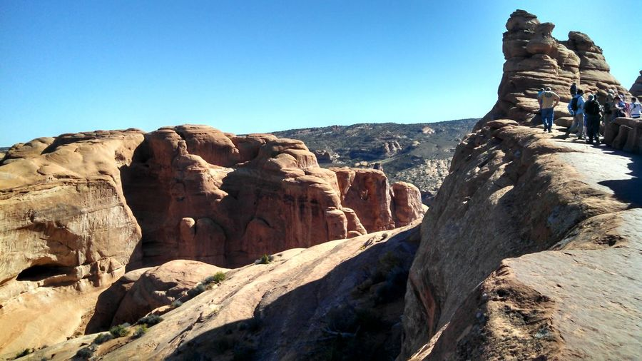 People on rock formations at arches national park