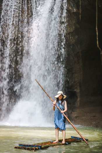 Full length of woman standing against waterfall
