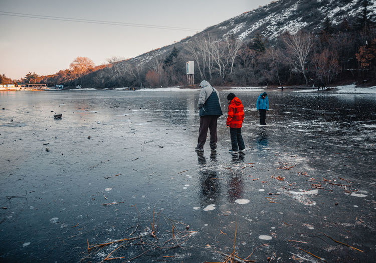Rear view of people walking on frozen lake against sky during winter