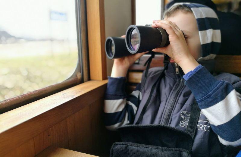Boy using binoculars in train