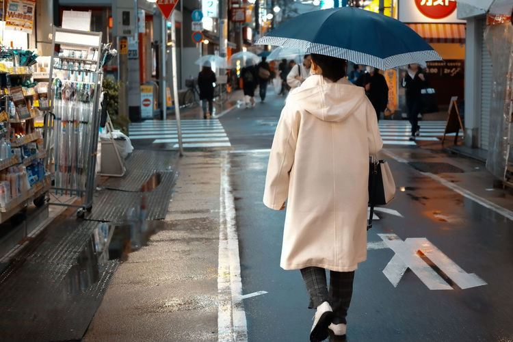 Rear view of woman walking on wet street in city