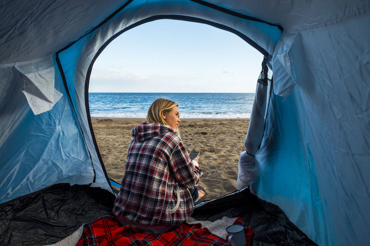 nice blonde use phone at camping in wind beach Freedom Tourist Adventure Beach Beauty In Nature Day Enjoyment Getting Away From It All Horizon Over Water Lifestyles Nature Positive Vibes Real People Relaxation Scenics Sea Sitting Tent Tranquility Travel Two People Vacations Water Weekend Activities Women