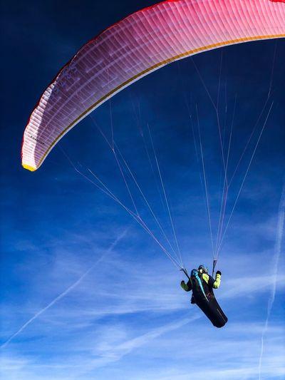 Woman paragliding against blue sky