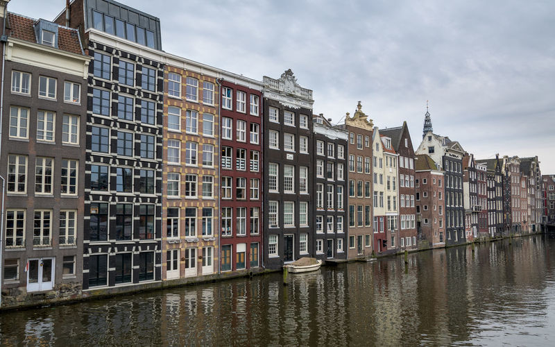 Buildings by canal against sky