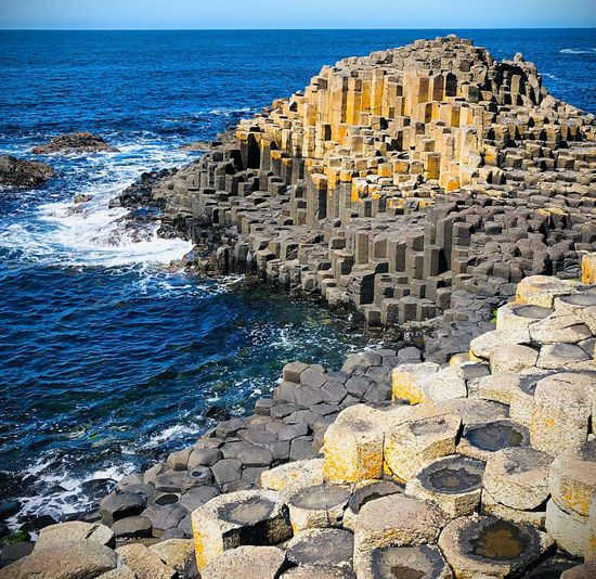 Giant's Causeway Waves Pentagons Hexagons Bushmills Northern Ireland Giant's Causeway Sea Water Rock Beach Land Nature Beauty In Nature Rock - Object Solid Sky Scenics - Nature Sunlight Tranquility Tranquil Scene Day No People Rock Formation Outdoors Horizon Over Water